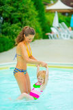 Mother and baby girl playing in swimming pool. Happy mother and baby girl playing in swimming pool royalty free stock image