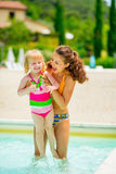 Mother and baby girl playing in swimming pool Royalty Free Stock Photography