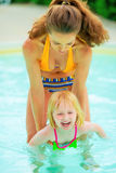 Mother and baby girl playing in swimming pool. Portrait of mother and baby girl playing in swimming pool royalty free stock photo