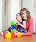 Mother and baby girl plays with blocks in home Royalty Free Stock Image