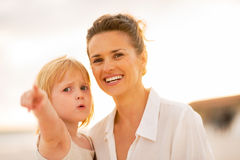 Mother and baby girl pointing while on beach Royalty Free Stock Image