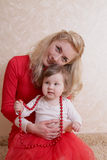 Mother and baby girl with red beads Royalty Free Stock Image
