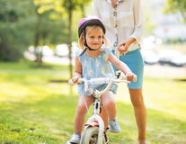 Mother and baby girl riding bicycle outdoors Stock Images