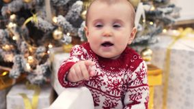 Mother with baby girl on rocking deer toy during Christmas eve stock footage