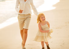 Mother and baby girl running on the beach Stock Photography