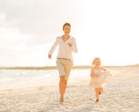 Mother and baby girl running on the beach Stock Photo