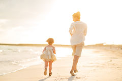 Mother and baby girl running on the beach Royalty Free Stock Photo