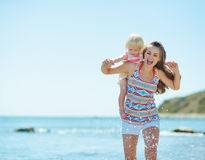 Mother and baby girl running on sea coast Royalty Free Stock Photography