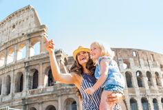 Mother and baby girl sightseeing near colosseum. Happy mother and baby girl sightseeing near colosseum in rome, italy Royalty Free Stock Photos