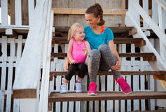 Mother and baby girl sitting on stairs of beach house Royalty Free Stock Photos
