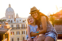 Mother and baby girl sitting on street in rome Stock Photos