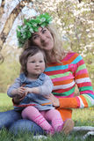 Mother and baby girl sitting under spring tree Royalty Free Stock Image