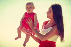 Woman hugging baby on beach near water Royalty Free Stock Photography