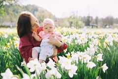 Mother and baby girl in spring park among blossom field stock photos