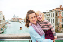 Mother and baby girl standing on bridge in venice Stock Photo