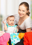 Mother and baby girl with suitcase and clothes ready for traveli Royalty Free Stock Photo