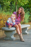 Mother and baby girl talking cell phone in park Royalty Free Stock Image