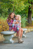 Mother and baby girl talking cell phone in park Royalty Free Stock Images