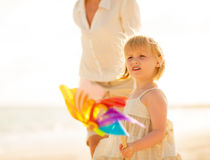 Mother and baby girl with toy windmill walking Stock Image