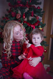 Mother and baby girl under Christmas tree Royalty Free Stock Images