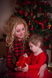 Mother and baby girl under Christmas tree Stock Photos