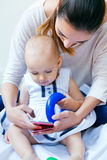 Mother and baby girl using a smartphone at home Stock Photos