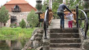 Mother and baby girl walk on stone stair bridge in park. 4K stock footage