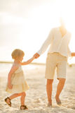 Mother and baby girl walking on the beach Royalty Free Stock Photos