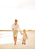 Mother and baby girl walking on the beach Stock Image