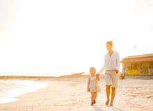 Mother and baby girl walking on beach Stock Photos