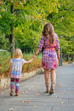 Mother and baby girl walking in city park Royalty Free Stock Photos