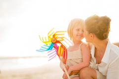 Mother and baby girl with windmill toy on beach Stock Images