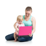 Mother and baby girl working at laptop Royalty Free Stock Photos