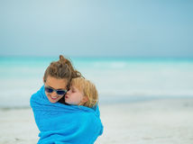 Mother and baby girl wrapped in towel on beach Royalty Free Stock Image