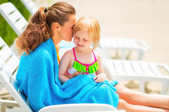 Mother and baby girl wrapped in towel on sunbed Stock Image
