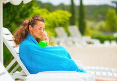 Mother and baby girl wrapped in towel on sunbed Royalty Free Stock Image