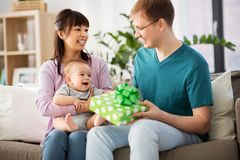 Mother with baby giving birthday present to father. Family, parenthood and fathers day concept - happy mother with baby boy giving birthday present to father at stock photo