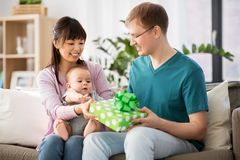 Mother with baby giving birthday present to father. Family, parenthood and fathers day concept - happy mother with baby boy giving birthday present to father at royalty free stock photos