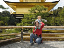 Mother and baby by Golden Pavilion; Kyoto, Japan. Happy mother and her baby by Golden Pavilion (Kinkakuji); Kyoto, Japan. Middle-aged caucasian woman holds her Royalty Free Stock Images
