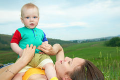 Mother with baby on green grass Stock Image