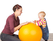 Mother and baby with a gym ball. Mother encouraging her young toddler, who has delayed motor activity disability, to stand using a gym ball Stock Photography