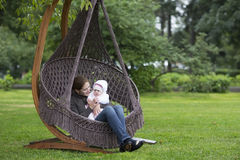 Mother and baby in a hanging chair in the park. Young mother and baby in a hanging chair in the park Stock Images