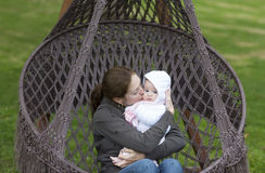 Mother and baby in a hanging chair in the park. Young mother and baby in a hanging chair in the park stock photos
