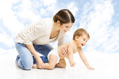 Mother baby happy playing. Child in diaper crawling over sky background royalty free stock images