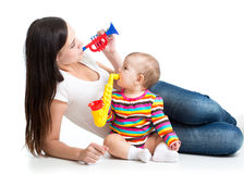 Mother and baby having fun with musical toys. Isolated on white background Royalty Free Stock Photos