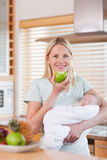 Mother with baby on her arms having an apple Royalty Free Stock Image