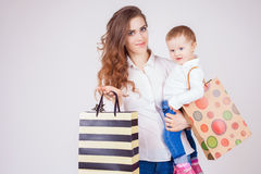 Mother and baby holding bags with purchases and toys. Shopping with child. They walking and looking at camera. Fashion baby clothes. Jeans. Boots, shoes. Today Stock Photos