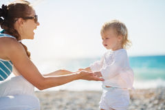 Mother and baby holding hands on beach Stock Image