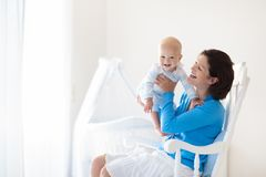 Mother and baby at home. Mom and child in bedroom. royalty free stock photos