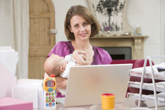 Mother and baby in home office stock photos
